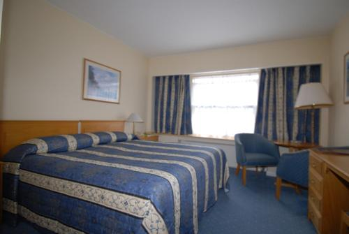 A bed or beds in a room at Oaklands Lodge Hotel