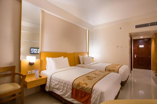 A bed or beds in a room at Golden Palace Hotel Lombok