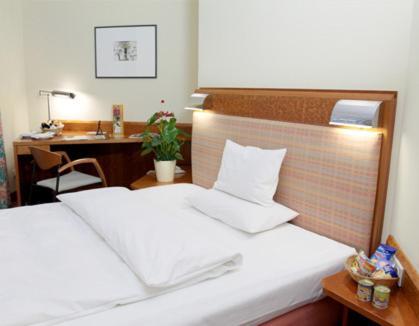 A bed or beds in a room at Altstadt Hotel zur Post Stralsund