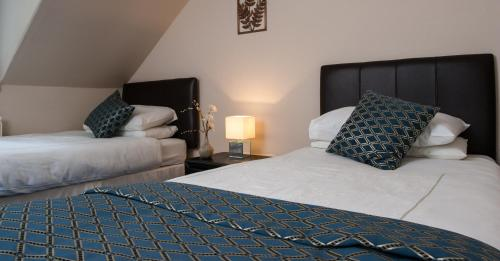 A bed or beds in a room at The Cnoc Hotel
