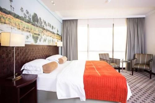 A bed or beds in a room at Phakalane Golf Estate Hotel Resort