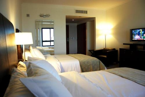 A bed or beds in a room at Ros Tower Hotel