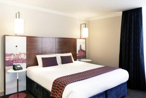 A bed or beds in a room at Mercure Cardiff Holland House Hotel & Spa