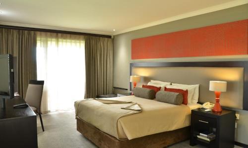Кровать или кровати в номере Cresta Riley's Hotel