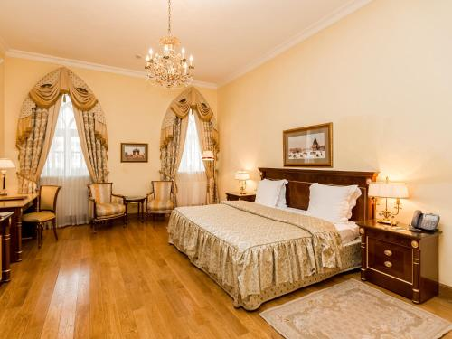 A bed or beds in a room at Petroff Palace Boutique Hotel