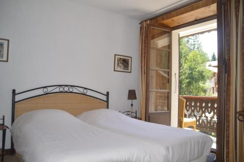 A bed or beds in a room at Hotel Le Genepy