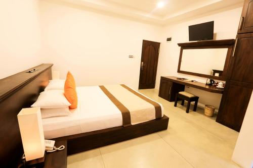 A bed or beds in a room at Rajarata Hotel
