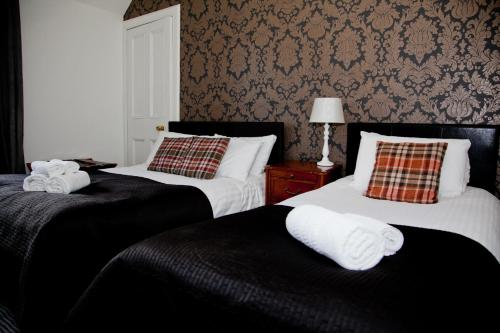 A bed or beds in a room at Richmond House Hotel