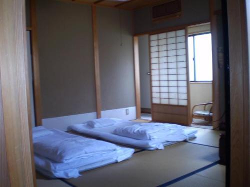 A bed or beds in a room at Ryokan Kyoka