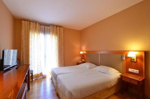 Een bed of bedden in een kamer bij Hotel Spa Acevi Val d'Aran