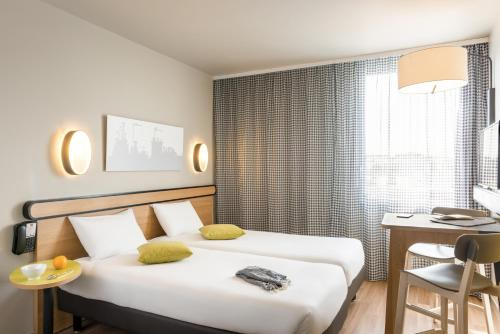 A bed or beds in a room at Aparthotel Adagio Access Paris Massy Gare