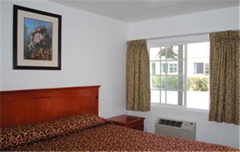 A bed or beds in a room at Rose Bowl Motel