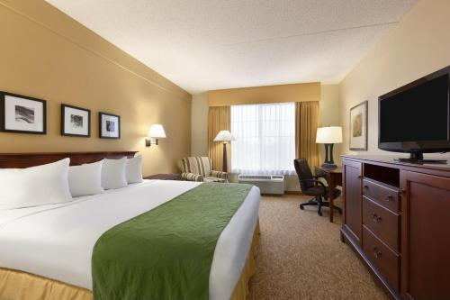A bed or beds in a room at Country Inn & Suites by Radisson, Mesa, AZ