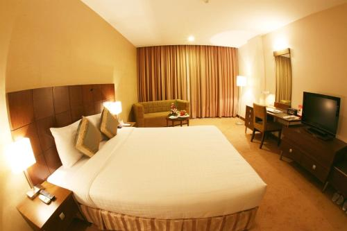 A bed or beds in a room at Aurora Hotel Plaza