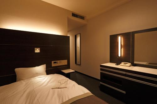 A bed or beds in a room at Kusatsu Estopia Hotel