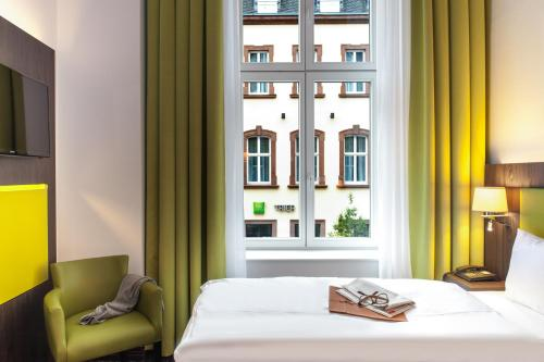 A bed or beds in a room at Ibis Styles Trier