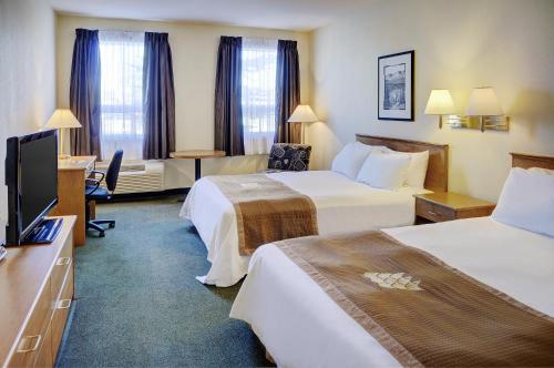 A bed or beds in a room at Lakeview Inns & Suites - Okotoks