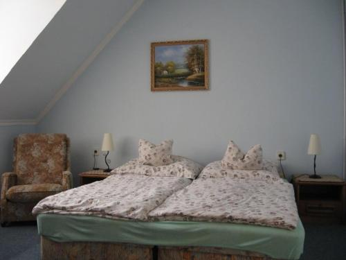 A bed or beds in a room at Mika Vendégház