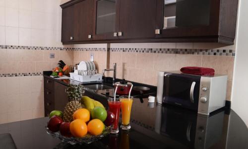 مطبخ أو مطبخ صغير في روز جاردن للشقق الفندقية - البرشاء