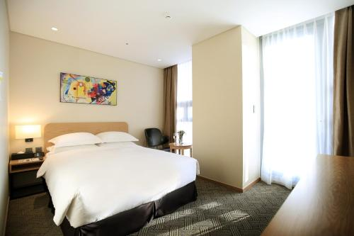 A bed or beds in a room at Best Western Haeundae Hotel