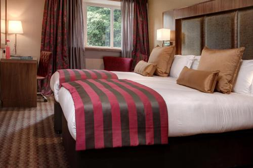 A bed or beds in a room at Donnington Manor Hotel