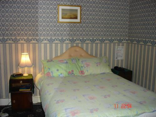 A bed or beds in a room at Victoria Park Hotel