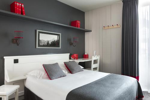 A bed or beds in a room at Le Faucigny - Hotel de Charme
