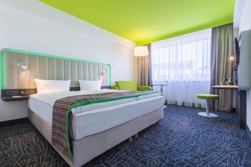 A bed or beds in a room at Park Inn by Radisson Nürnberg
