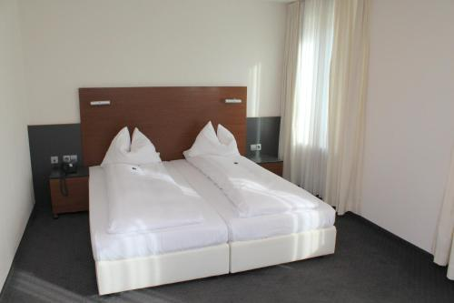 A bed or beds in a room at Hotel am Hirschgarten