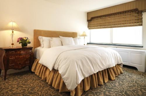 A bed or beds in a room at The Kimberly Hotel & Suites