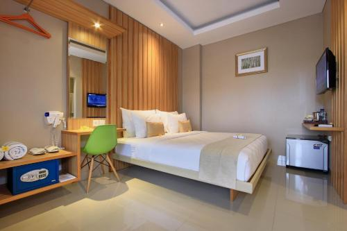 A bed or beds in a room at Puri Padma Hotel