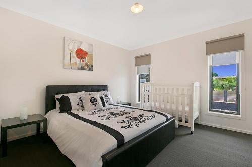 A bed or beds in a room at Palm Grove Beach House Dromana