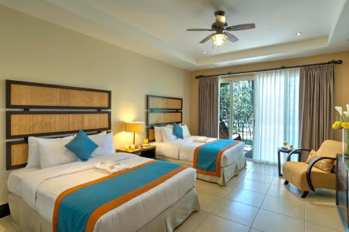 A bed or beds in a room at Casa Conde Beach Front Hotel