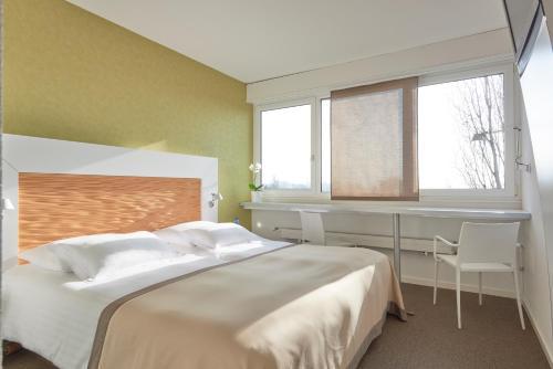 Ein Bett oder Betten in einem Zimmer der Unterkunft Le Leman Hotel