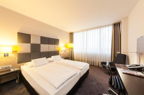 A bed or beds in a room at Select Hotel Berlin Spiegelturm