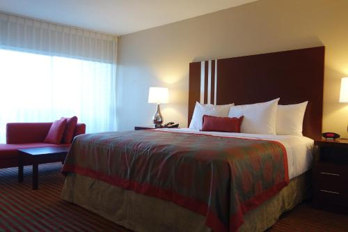 A bed or beds in a room at Ramada by Wyndham Sacramento