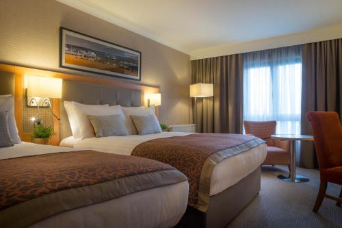 A bed or beds in a room at Clayton Hotel Leopardstown