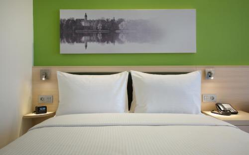 A bed or beds in a room at Hampton by Hilton Minsk City Centre