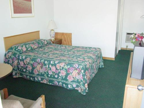 A bed or beds in a room at Monticello Inn - Monticello, Indiana