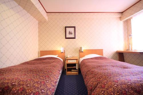 A bed or beds in a room at Niigata Station Hotel