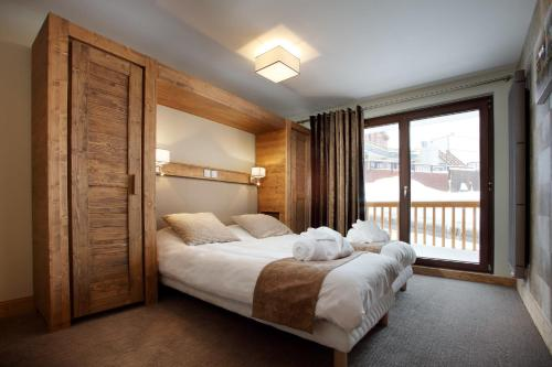 A bed or beds in a room at Chalet des Neiges -La Source des Arcs