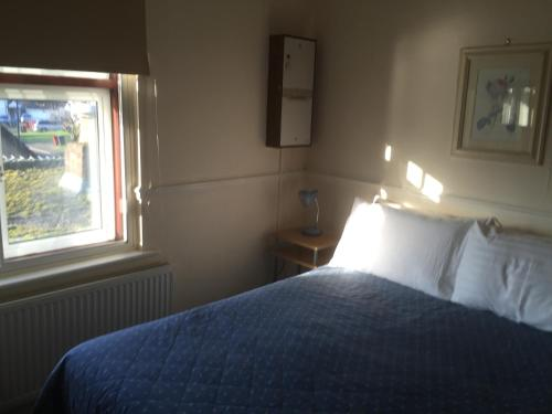 A bed or beds in a room at Colnbrook Lodge Guest House