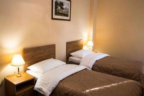 Кровать или кровати в номере Малетон Отель (Анохина)