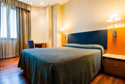 Un pat sau paturi într-o cameră la Hotel Villacarlos