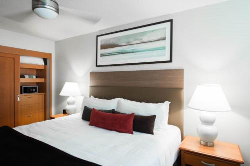 A bed or beds in a room at West Coast Suites at UBC