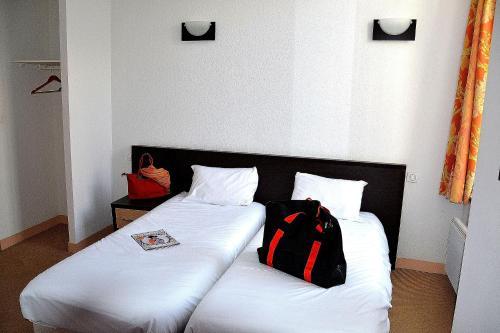 Un ou plusieurs lits dans un hébergement de l'établissement Hotel Les Bénédictins