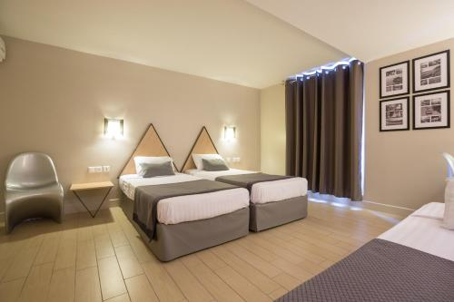 A bed or beds in a room at Hôtel Amirauté