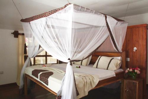 A bed or beds in a room at Kinazi Upepo Beach Hotel