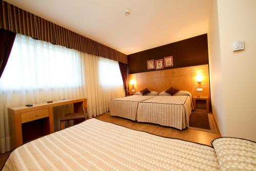 A bed or beds in a room at Hotel Condes De Lemos