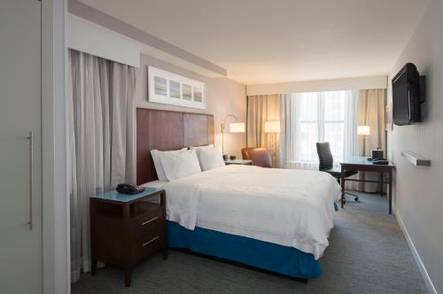 A bed or beds in a room at Hampton Inn Seaport Financial District